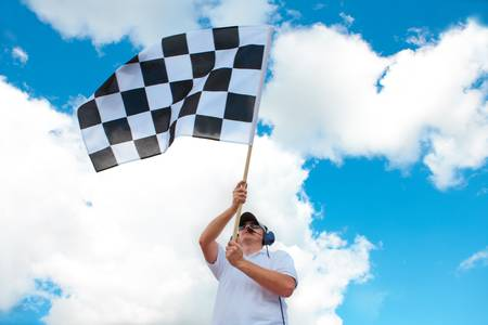 headset symbol: Man with headset holding and waving a checkered flag on a raceway