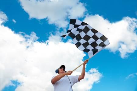 bandera carrera: El hombre con auriculares sosteniendo y agitando una bandera a cuadros en una pista de rodadura Foto de archivo