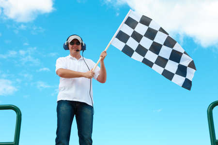 Man with headset holding and waving a checkered flag on a raceway photo