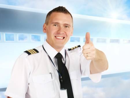 piloto de avion: Piloto de l�nea a�rea Alegre llevar uniforme con epauletes mostrando el pulgar hacia arriba gesto de aprobaci�n, de pie sobre fondo moderno.