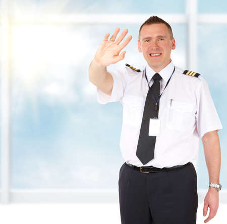 Cheerful airline pilot wearing uniform with epaulettes sending greets with hand, standing at the airports big window photo