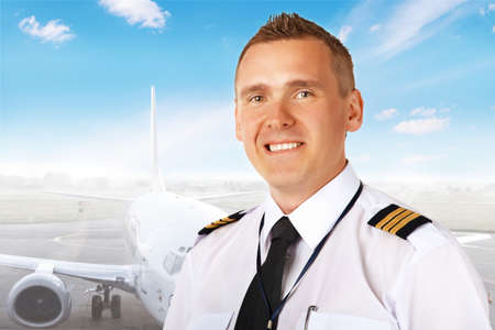 aircrew: Airline pilot wearing uniform with epaulettes with passenger aircraft in background