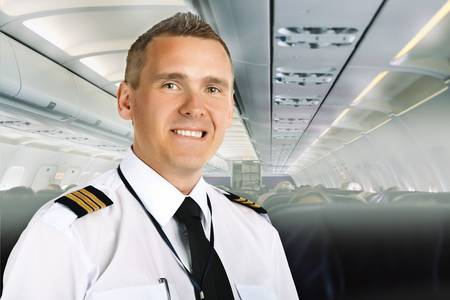 epaulets: Airline pilot wearing uniform with epaulettes on board of passenger aircraft.