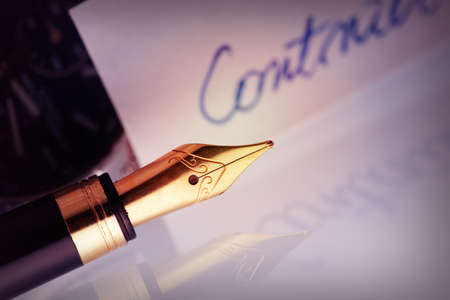 nib: Pen with golden nib with contract document in the background Stock Photo