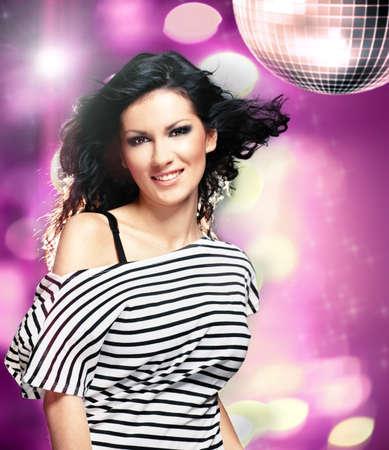 Beautiful woman in a nightclub with big disco ball photo