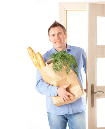 Man with shopping bag with bread and vegetables inside entering room photo