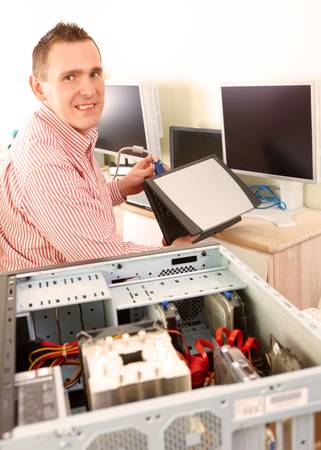 Repairman working with computer with laptop in hands  Monitors and other laptops in the background waiting for service  photo