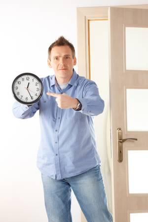 punctual: El hombre enojado que muestra una situaci�n de reloj com�n cuando una mujer se prepara para largo o cuando su jefe es muy puntual Foto de archivo
