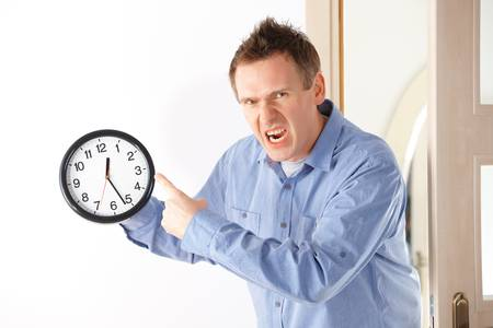 impatience: Angry man showing a clock  Common situation when a woman prepares herself to long or when your boss is quite punctual  Stock Photo