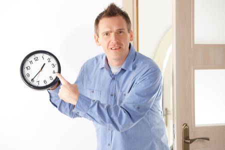 punctual: Angry man showing a clock  Common situation when a woman prepares herself to long or when your boss is quite punctual  Stock Photo