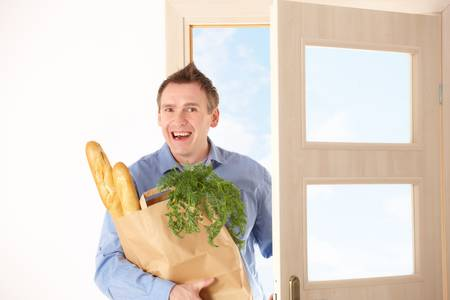 Man with shopping bag with bread and vegetables entering house  photo