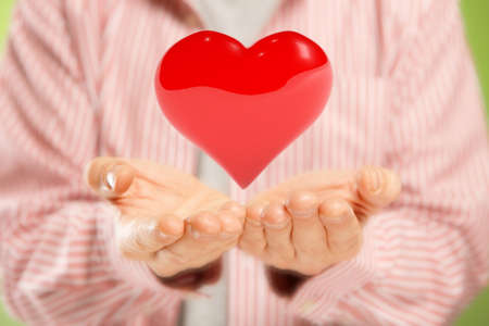 Open hands giving big red heart  Concept of pure love or great health photo