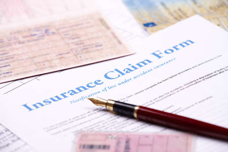 reimbursement: Blank insurance claim form and other papers like ID or vehicle documents and pen lying on desk Stock Photo