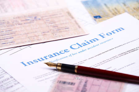 financial questions: Blank insurance claim form and other papers like ID or vehicle documents and pen lying on desk Stock Photo