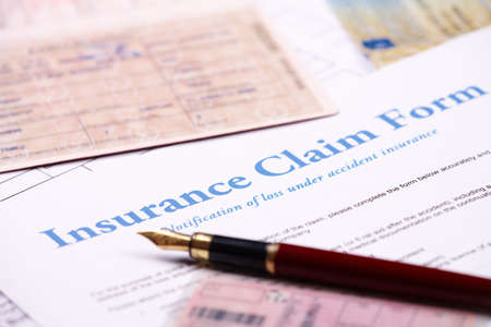 Blank insurance claim form and other papers like ID or vehicle documents and pen lying on desk Stock Photo