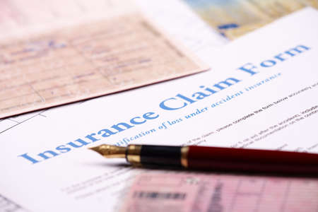 Blank insurance claim form and other papers like ID or vehicle documents and pen lying on desk photo