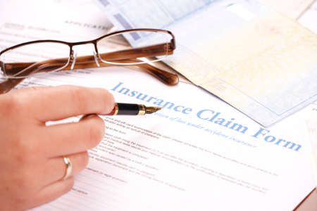 policies: Hand filling in insurance claim form. Glases and other papers like ID or vehicle documents in the background