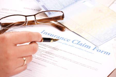 reclamo: Mano de llenado en forma de reclamaci�n de seguro. Vidrios y otros documentos, como documentos de identidad o de un veh�culo en el fondo