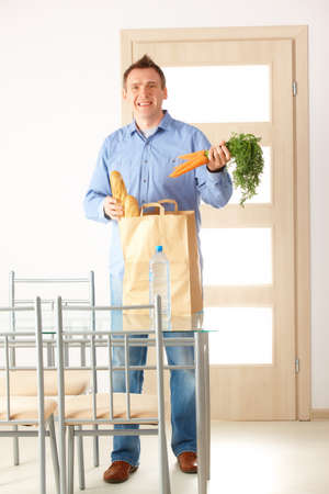 Man with shopping bag with bread and vegetables unpacking in home Stock Photo - 13174936