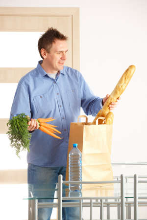 Man with shopping bag with bread and vegetables unpacking in home photo