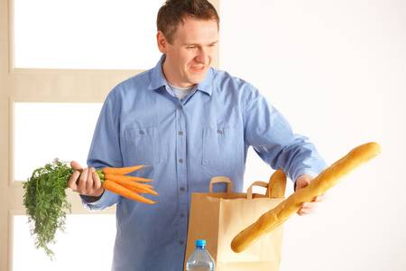 Man with shopping bag with bread and vegetables unpacking in home Stock Photo - 13174935