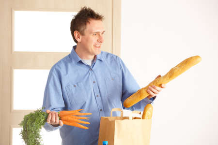 Man with shopping bag with bread and vegetables unpacking in home Stock Photo - 13174932