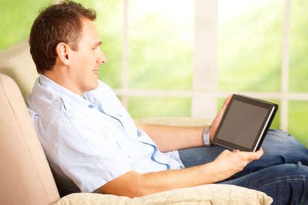 big window: Man met behulp van tablet, zittend op de sofa in huis met groot raam op de achtergrond Stockfoto