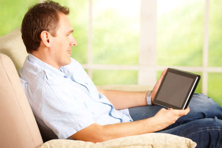 computer model: Man using tablet, sitting on sofa in home with big window in background