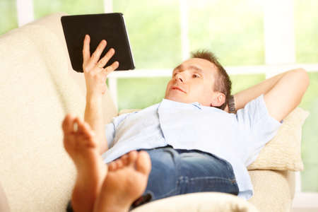 Man relaxing with tablet, laying on sofa in home with big window in background Stock Photo - 13174957