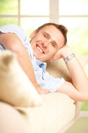 Portrait of a man relaxing on sofa in home and smiling. Stock Photo - 13174941