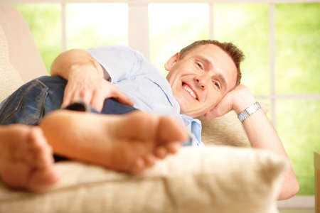Portrait of a man relaxing on sofa in home and smiling. photo