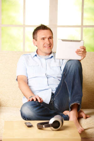 Man using tablet, sitting on sofa in home with big window in background, headphones on table Stock Photo - 13174947