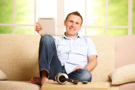 Man using tablet, sitting on sofa in home with big window in background, headphones on table photo