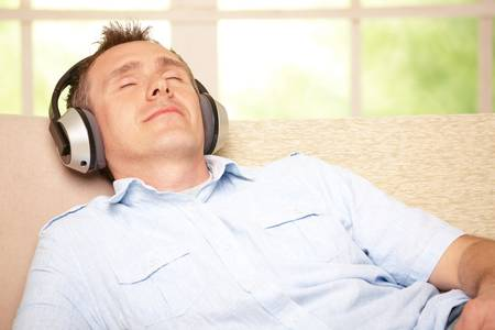 Man listening music with cordless headphones sitting on sofa at home  photo