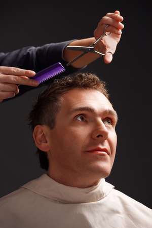 Barber cutting hair with scissors and comb, a client is a young caucasian man Stock Photo