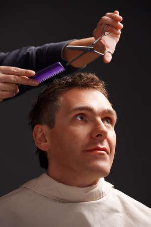 comb hair: Barber tagliare i capelli con forbici e pettine, un client � un giovane caucasico Archivio Fotografico