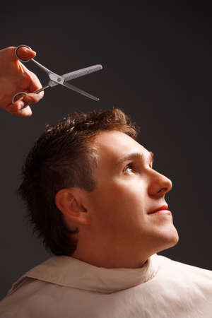 Barber cutting hair with scissors, a client is a young caucasian man Stock Photo - 13571190