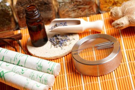 Acupuncture needles, moxa sticks, lavender petals with macerated oil, giner and herbs in jars TCM Traditional Chinese Medicine concept photo