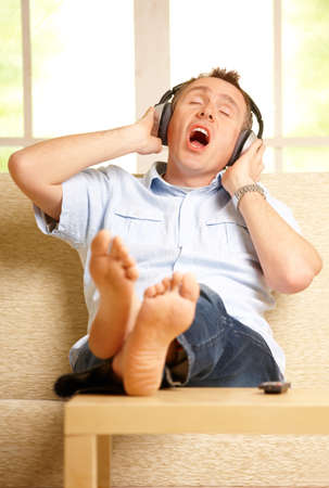 Man listening music with headphones sitting on sofa at home and singing photo