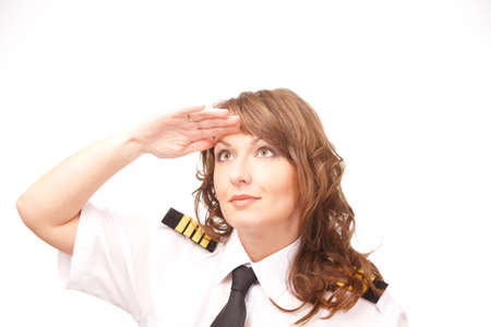 Beautiful woman pilot wearing uniform with epauletes looking ahead, standing isolated on white background   photo