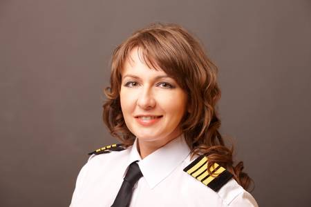 Beautiful woman pilot wearing uniform with epauletes looking ahead photo