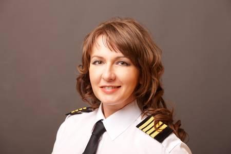 piloto: Piloto de la mujer hermosa que desgasta uniforme con epauletes mirando hacia el futuro