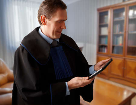 justness: Attorney wearing classic gown with tablet in his office