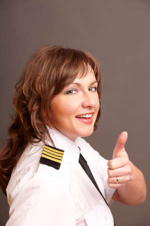 Beautiful airline pilot wearing uniform with epauletes showing thumb up gesture of approval photo
