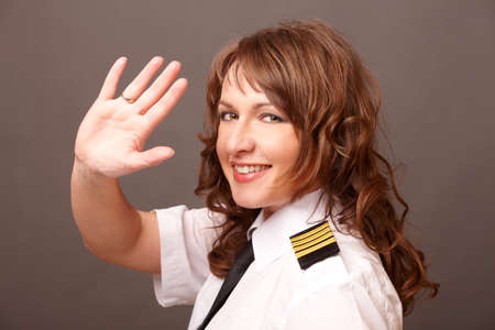 Beautiful woman pilot wearing uniform with epaulettes waving with her hand photo