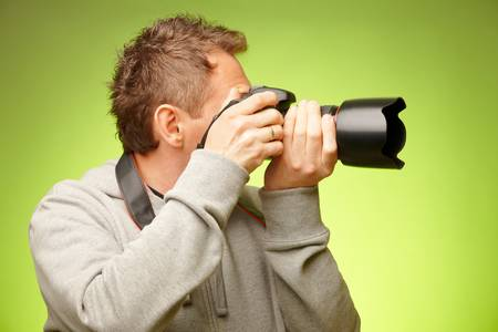 Male photographer taking photos with DSLR digital camera, side view photo