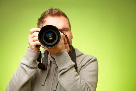 Male photographer taking photos with DSLR digital camera photo