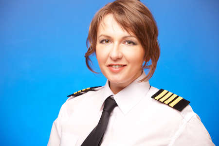 aircrew: Beautiful woman pilot wearing uniform with epauletes, looking ahead, standing on blue background