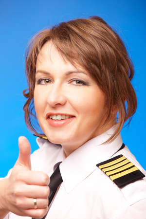 airline uniform: Beautiful airline pilot wearing uniform with epauletes showing thumb up gesture of approval, standing on blue background  Stock Photo