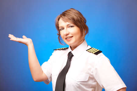 Beautiful woman pilot wearing uniform with epaulettes, presenting something on her hand, standing on blue background   photo